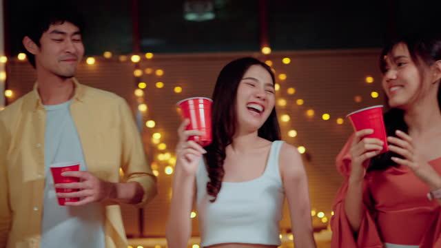 若い男女がダンスを踊り、パーティーで飲み物を乾杯 - 使い捨てコップ点の映像素材/bロール