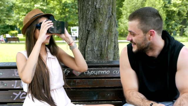 Jonge mannen en vrouw plezier met VR-bril in het park