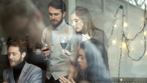 vídeos y material grabado en eventos de stock de young men and women at christmas dinner party - mesa de comedor