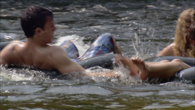 young men and women floating on inner tubes splashing each other / farmington river, connecticut - rubber ring stock videos & royalty-free footage
