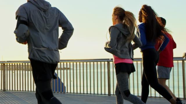 若い男性と女性が橋の上にジョギング - ジョギング点の映像素材/bロール