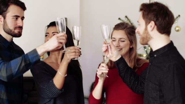Young men and women toasting and drinking champagne during Christmas party