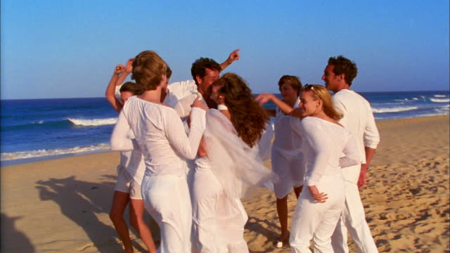vídeos de stock e filmes b-roll de young men and women wearing white clothing dance on the beach. - noivo papel em casamento