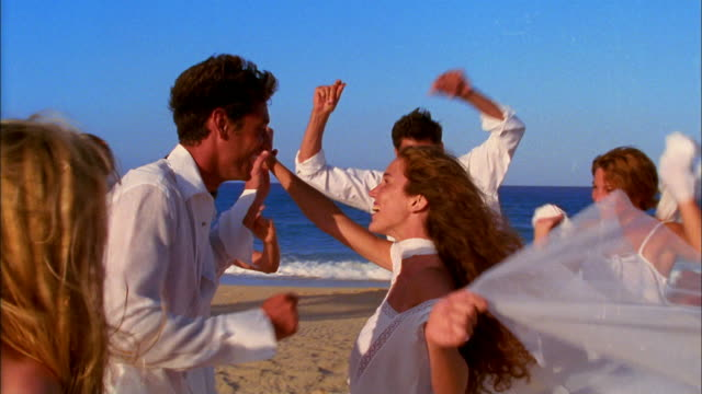 Young men and women wearing white clothing dance on the beach.