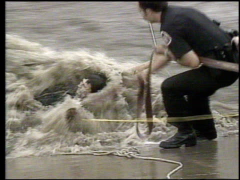 vídeos de stock e filmes b-roll de / young men are rescued after skateboarding in an arroyo, flood control ditch, when water came rushing down from the mountains and swept them away /... - puxar