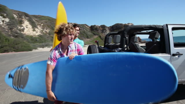 Young men arriving at beach with surfboards
