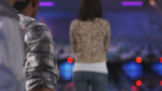 young men at a bowling alley watching a young woman bowl and shake her butt - ボウリング点の映像素材/bロール