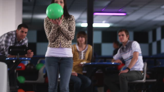 young men at a bowling alley watching a young woman bowl and shake her butt