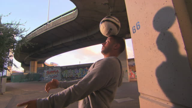 vídeos de stock, filmes e b-roll de cu young men balancing soccer ball on head and face standing under underpass, london, england, uk - stunt