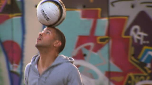 vídeos y material grabado en eventos de stock de cu pan young men bouncing soccer ball on head near graffiti wall, london, england, uk - truco