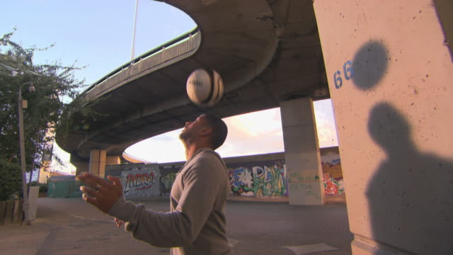 vídeos y material grabado en eventos de stock de cu young men bouncing soccer ball on head standing under underpass, london, england, uk - truco