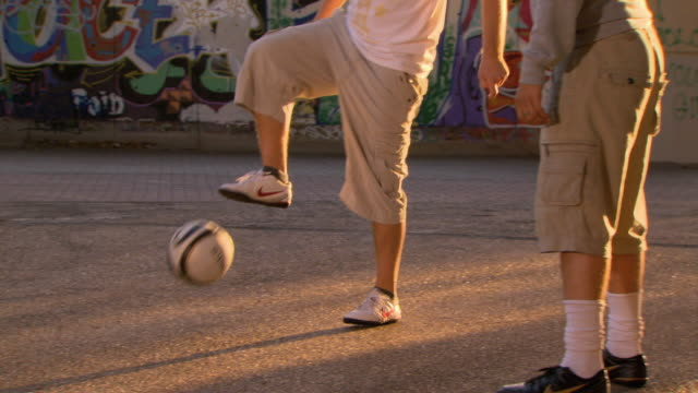 cu zo ms pan tu td young men bouncing soccer ball with feet by graffiti wall, london, england, uk - stunt stock videos & royalty-free footage