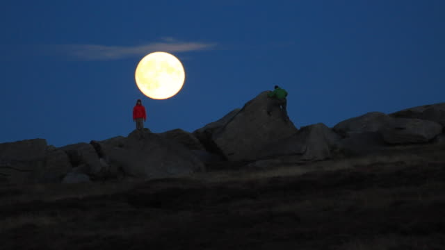young men climb boulders at night under a full moon while bouldering. - sweatshirt stock videos and b-roll footage