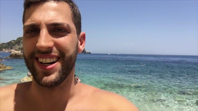 junge männer machen einen video-chat / filmen am strand - webcam stock-videos und b-roll-filmmaterial