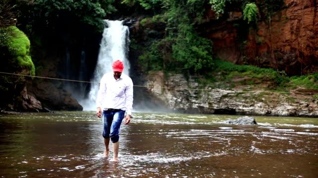 Young Men doing Warrior Pose yoga near waterfall