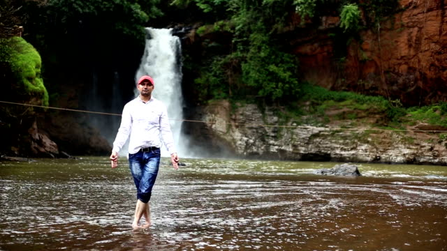 young men doing yoga near waterfall - mudra stock videos & royalty-free footage
