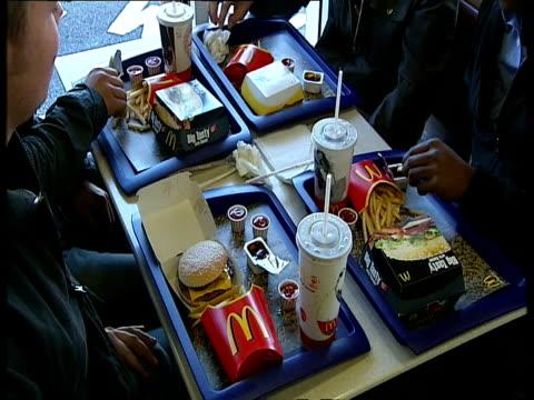 vidéos et rushes de young men eating meal at mcdonald's / sheffield, england - montage séquentiel