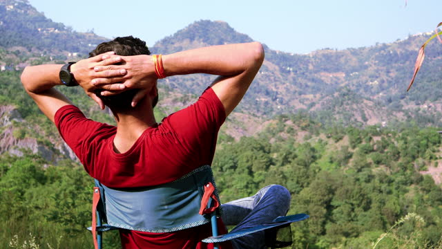 山で新鮮な空気を楽しむ若い男性 - indian ethnicity点の映像素材/bロール