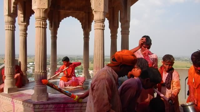 vídeos y material grabado en eventos de stock de young men getting ready and filling their water pistols / religious festivities and celebrations inside the temple complex in nandgaon mathura the... - krishna