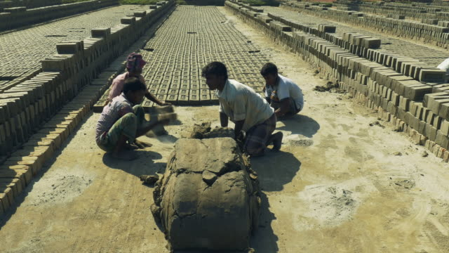 Young men in Bangladesh use simple wooden moulds to fashion bricks from a simple clay and water mix there actions are fast and rhythmical
