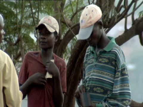 ms young men in baseball caps exchange money on kigali street / kigali, rwanda - キガリ点の映像素材/bロール