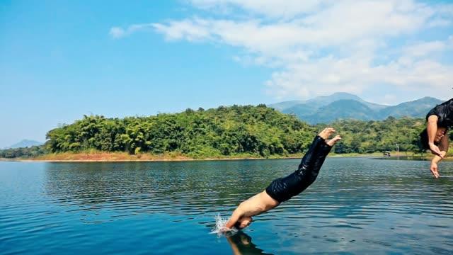 stockvideo's en b-roll-footage met jonge mannen springen vanaf pier in lake samen, vrienden springen van de steiger bij het meer op een zonnige dag - steiger pier
