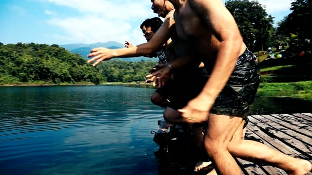 young  men jumping from pier into lake together,friends jumping off the jetty at the lake on a sunny day - jetty stock videos & royalty-free footage