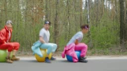 Young men jumping on bright balls