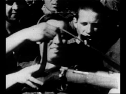 young men load rifles during spanish civil war / soldier teaches woman how to load rifle / woman hoists rifle to her shoulder as men behind her watch... - civilperson bildbanksvideor och videomaterial från bakom kulisserna