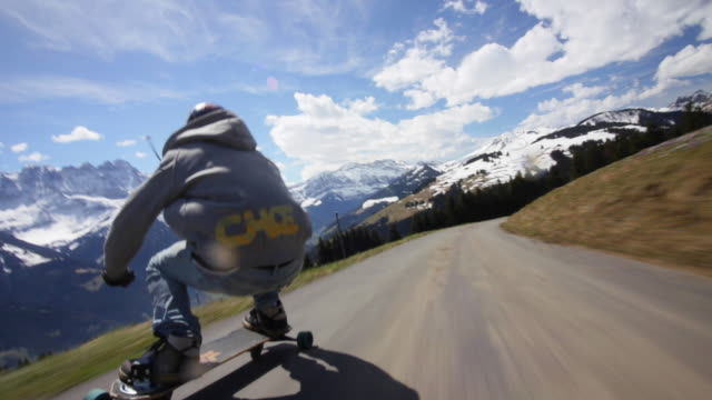 pov of young men longboard skateboarding downhill on a mountain road. - jeans bildbanksvideor och videomaterial från bakom kulisserna