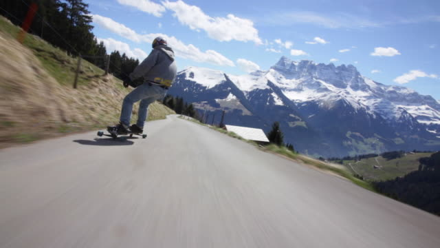 POV of young men longboard skateboarding downhill on a mountain road.