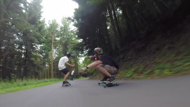 POV of young men longboard skateboarding downhill on a rural road hand off a drink.