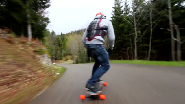 pov of young men longboard skateboarding downhill on a rural road. - inarcare la schiena video stock e b–roll