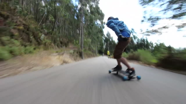 pov of young men longboard skateboarding downhill on a rural road. - courage stock videos & royalty-free footage