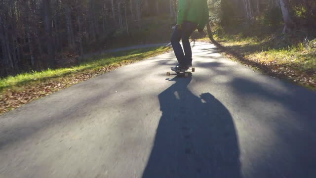 POV of young men longboard skateboarding downhill on a rural road.