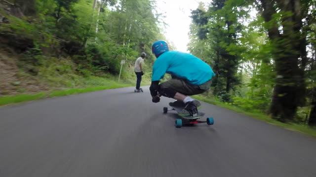 pov of young men longboard skateboarding downhill on a rural road. - longboarding stock videos & royalty-free footage