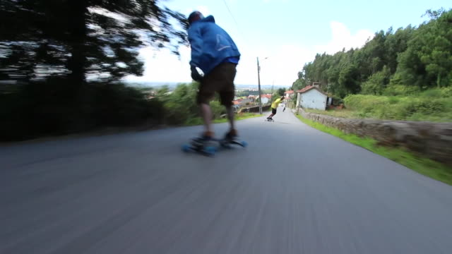 pov of young men longboard skateboarding into a rural town road. - shorts stock videos & royalty-free footage