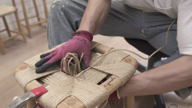 Young men make chairs in woodwork studio