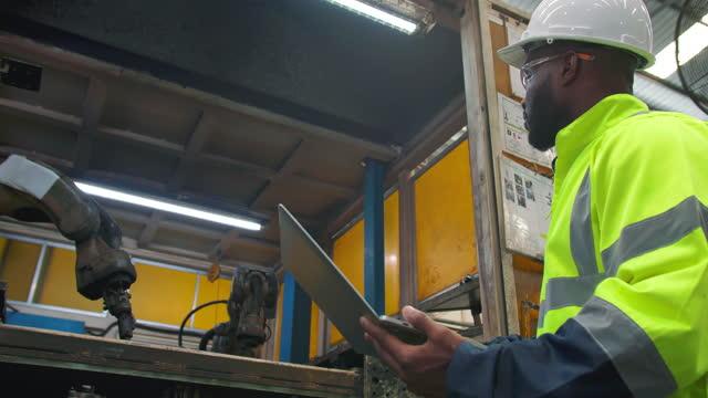 giovani uomini di etnia afroamericana di 30 anni, è ingegnere, usano computer portatile per la programmazione di braccio robotico e automazione del controllo del lavoro robotica nell'industria industriale di fabbrica. industria 4.0 - azionare video stock e b–roll