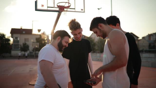 vídeos y material grabado en eventos de stock de jóvenes en el campo de baloncesto con teléfono - sports training
