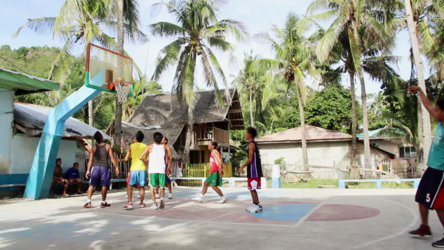 ws pan young men play basketball on palm tree line outdoor court / apo island, negros oriental, philippines - philippines stock videos & royalty-free footage