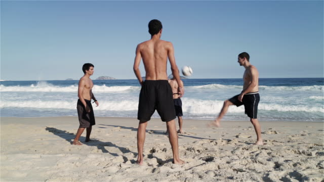 ws young men play football on ipanema beach / rio de janeiro, brazil - 上半身裸点の映像素材/bロール