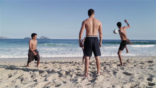 vidéos et rushes de ws young men play football on ipanema beach / rio de janeiro, brazil - activité