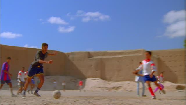 vidéos et rushes de young men play soccer on a dusty field. available in hd. - moyen oriental