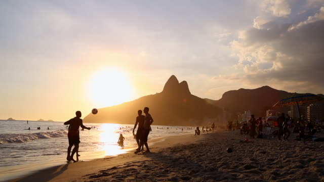 young men playing ball during sunset - copacabana stock videos & royalty-free footage