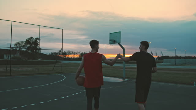 ms young men playing basketball on outdoor basketball court at dusk. two friends walking off outdoor basketball. - male friendship stock videos & royalty-free footage