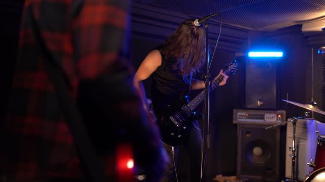 stockvideo's en b-roll-footage met jonge mensen die elektrische gitaar op repetitie met band in muziekstudio spelen - rock