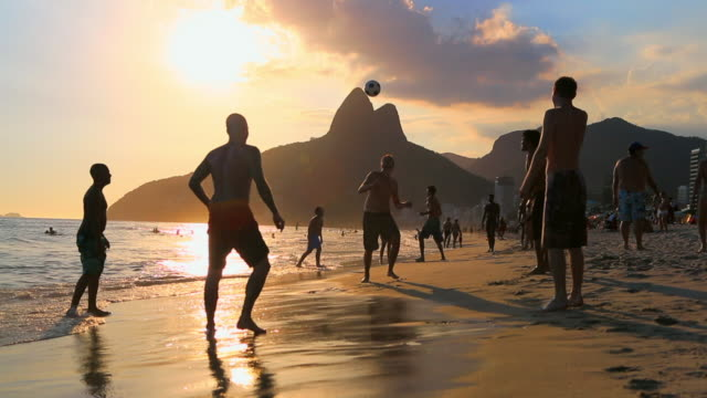 vídeos de stock, filmes e b-roll de young men playing football on beach at sunset - praia