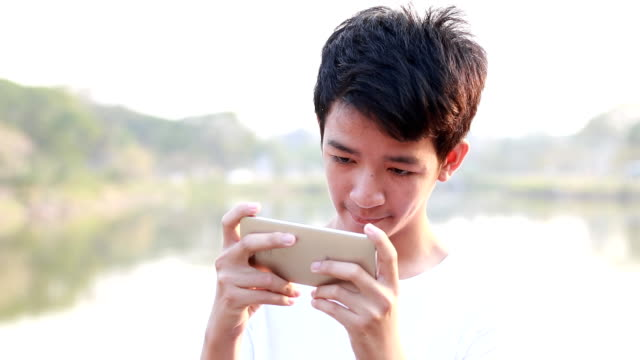 young men playing game on smart phone - one teenage boy only stock videos & royalty-free footage