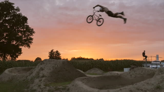 young men racing their bmx bike bicycle on an outdoor dirt track race. - bicycle trail outdoor sports stock videos & royalty-free footage